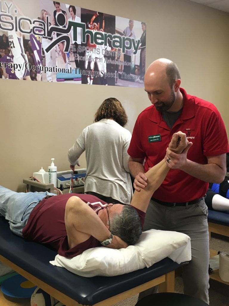 Physical Therapist Assistant stretching a patient