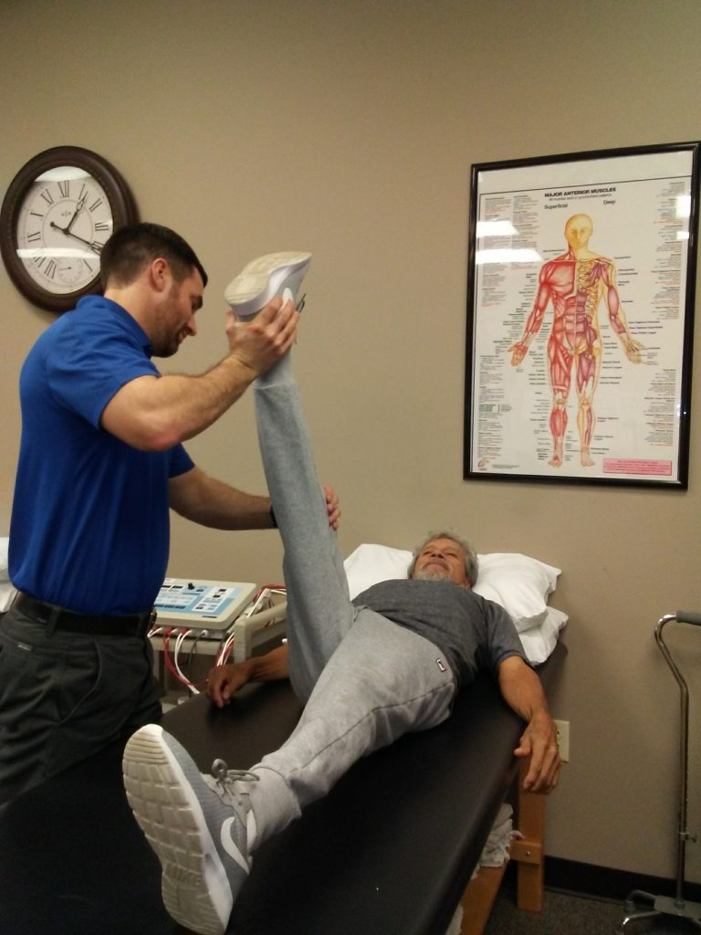 Physical Therapist stretching patient